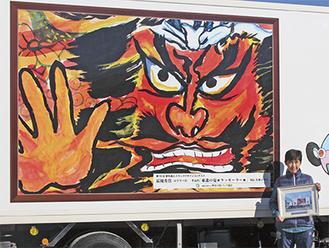 自分の作品が描かれたトラックを前に笑顔を見せる児島さん