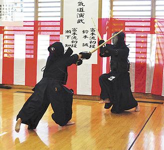 男性相手に果敢に攻め込む女性剣士(左)
