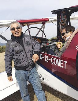 着陸直後のコメットを前に笑顔の山田さん(左)