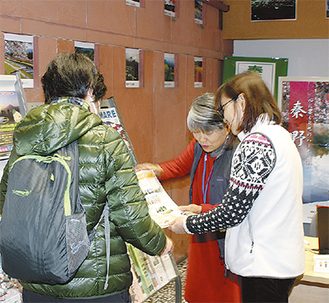 訪問者(左)対して資料を見せながら説明する案内所の2人のスタッフ