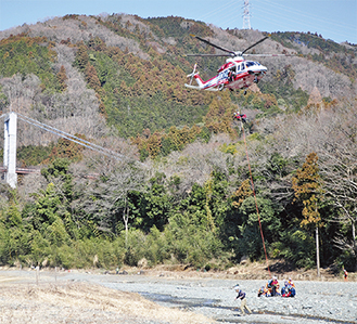 救助者を吊り上げる横浜市消防局のヘリ