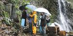 雨の中、祈りを捧げる会員ら