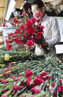 摘み取った花をまとめる今井さん