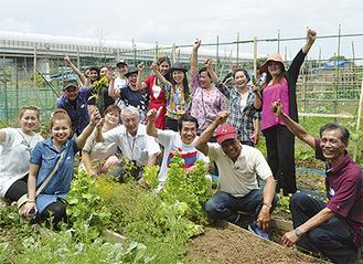 野菜を育てるラオス出身の人々。中央左が浅見さん。