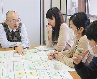 メディア活用戦略について考えるグループワークで、河井教授(左)からアドバイスを受ける職員ら