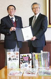 図書31冊と共に市長室を訪れた鶴井常務理事(右)