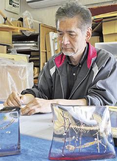 作業を進める三嶋さん。手前は本物の魚の骨を閉じ込めた作品。