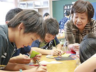 長寿会のメンバーに紙相撲の作り方を教わる子どもたち=7月7日