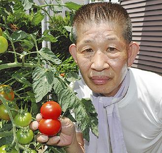 トマトを持つ富永さん