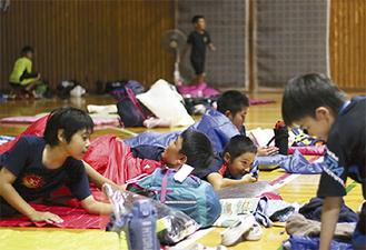 夜、体育館の床に敷いた寝袋に入る児童たち