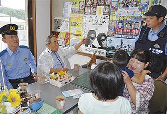 友の会の内藤会長(中央)、片山署長(左)と話す船見巡査部長と正美さん夫妻