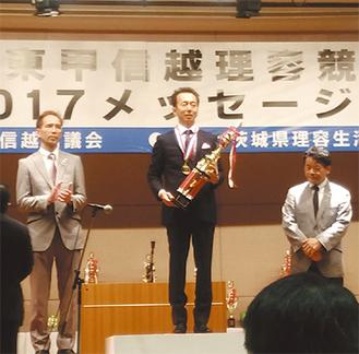 優勝トロフィーを手にする飯塚さん(中央)