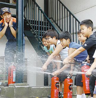 消防署員の合図で的に放水する児童たち