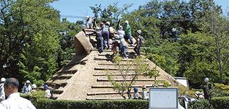 屋根に上り、最後の仕上げを行う参加者