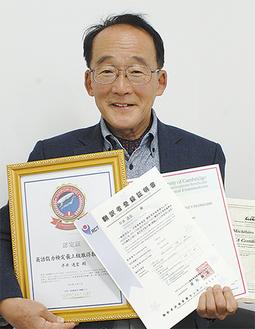 認定証や証明書を持つ平井さん