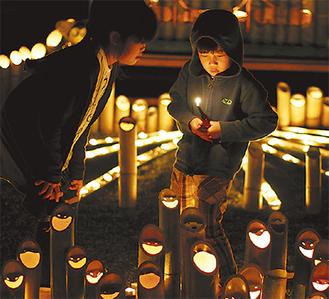 竹灯籠に点火する少年