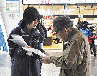 啓発品を手渡す小林主将(左)
