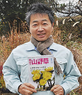雑誌を持つ村上さん
