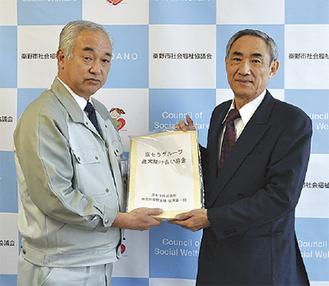 藤村会長に寄付金を手渡す西原工場長(左)