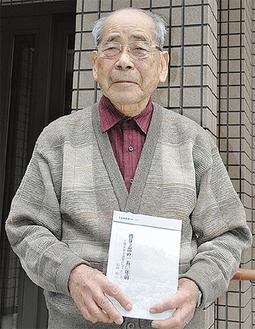 自治会館の前で本を手にする岩田さん