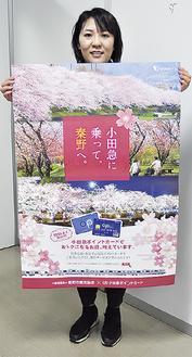 ポスターを持つ観光協会職員