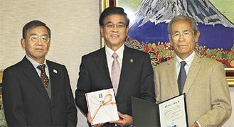 小清水会長(右)と石塚拓雄さん(左)が高橋市長に目録を手渡した