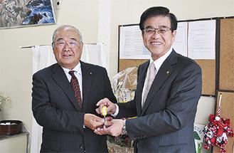 高橋市長から鍵を受け取る和田会長(左)