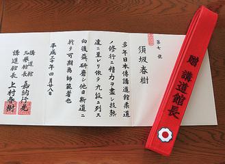 須坂さんに贈られた赤帯と表彰状