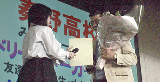 生徒から花束と似顔絵を受け取る腰塚さん(右)