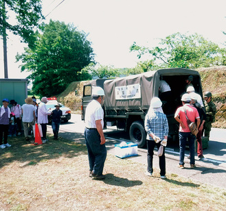 避難をするため人員輸送車に乗り込む住民(写真は市提供)