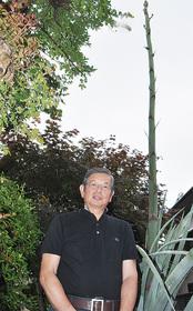 開花を待ちわびる高橋さん(6月11日撮影)