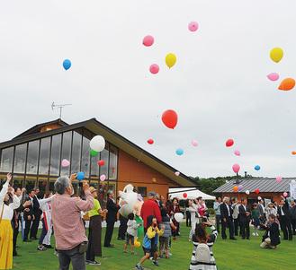 オープンを祝って風船を飛ばす式典の参加者