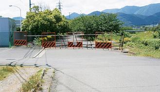 バリケードが設置されている市道14号線右奥に見えるのは塚原橋