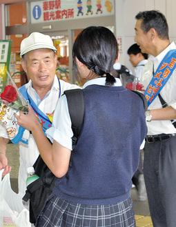秦野駅で学生に啓発品を渡す参加者