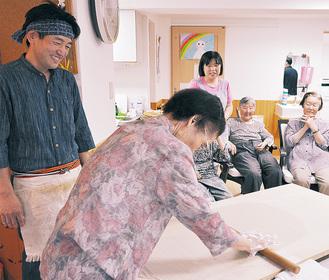 そば生地を伸ばす利用者と阪間さん(左)