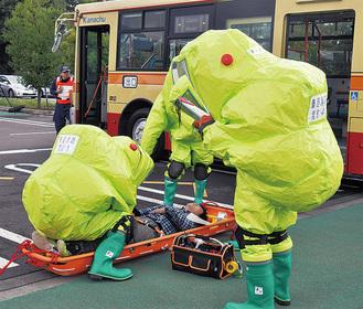 防護服を着てバスの乗客を救助する消防署員ら