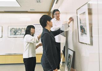 慎重に浮世絵を展示する学生