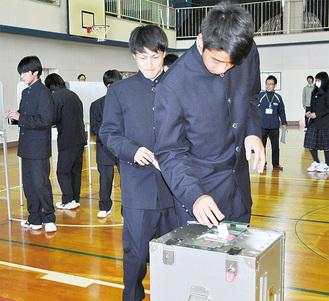 投票箱に投票用紙を入れる生徒ら