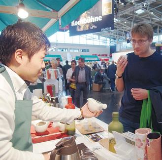 ドイツ・ミュンヘンのFOOD&LIFEの出展ブースで来場者に日本茶の魅力を伝える高梨晃さん(左)
