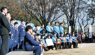 地域の人や学生、報道陣に祝福されるバスケ部と駅伝チーム