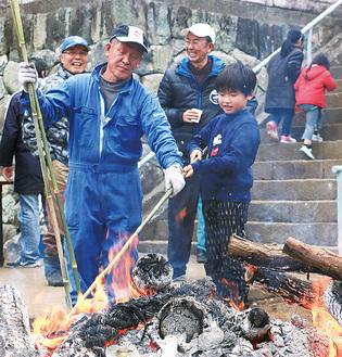 団子を焼く上村さんと子ども
