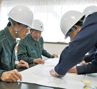 職員が地図に書き入れた通行止め箇所を確認する正副議長(左)