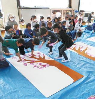 桜に見立てた手形を押した児童ら