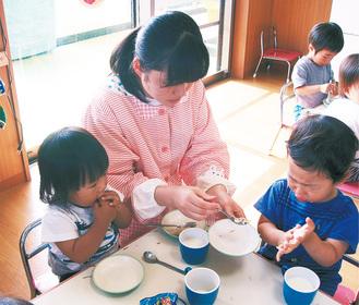 保育園で子どもたちと食事をする高校生