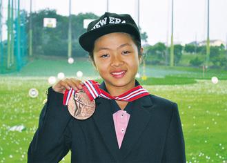 メダルを手に笑顔の田村さん