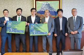 古川社長(左)や奥村監督(左から2番目)が高橋市長にチームのフラッグを手渡し、試合に向け抱負を語った