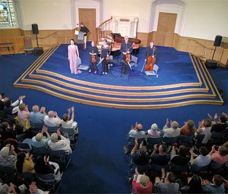 現地楽団と共演する岡本さん(ステージ左)
