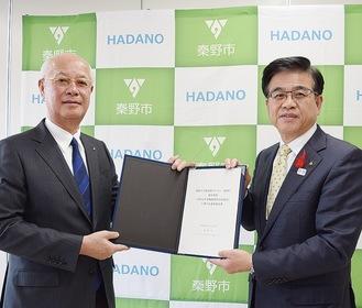 協定書をもつ脇本代表取締役(左)と高橋市長