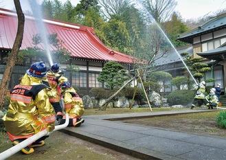 一斉放水する消防隊員