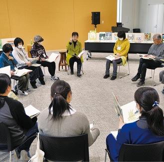 講師の中本さん(中央)の指導を受け絵本を読む受講生ら